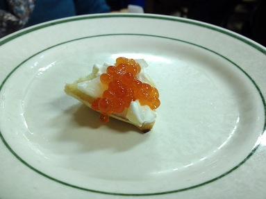 Photograph of red salmon caviar and sour cream on a piece of bialy
