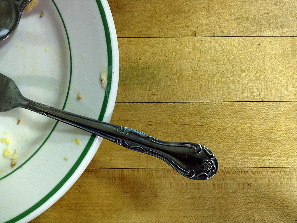 Photograph closeup of wooden table and metal fork and spoon on china plate