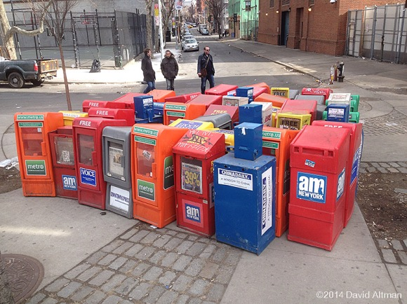 A group of newspaper dispensers on the sidewalk junction at Canal and Thompson Streets and Sixth Avenue.